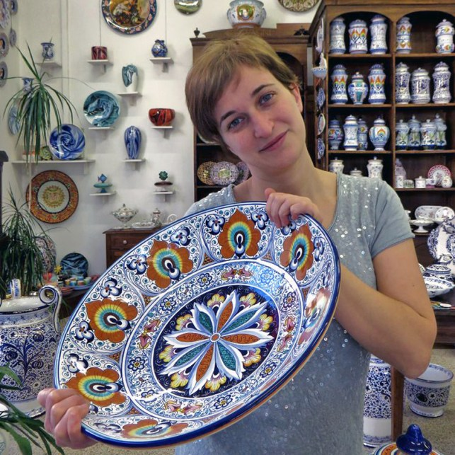 the artisan of ceramics Elisa Suzzi with hand decorated plate Pavona style - La Vecchia Faenza
