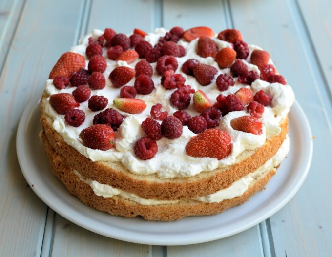When the cake is cold, carefully cut it into three slices, and place one slice on a serving plate; spoon a third of the cream over the cake, then add the strawberries and raspberries; continue to layer the cake this way, ending with the top which is also decorated with cream, strawberries and raspberries.