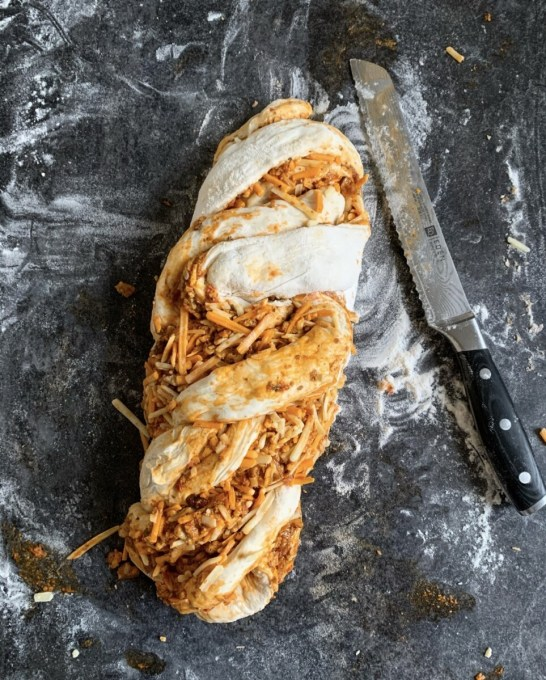Cut the rolled and filled dough in half right down the middle, so you have 2 long cut lengths, and then turn the filled dough over so the filling and layers are exposed. Twist the 2 lengths together into a simple plait shape. Sprinkle the Nigella seeds over the top of the Babka.