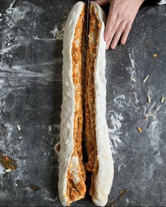 Cut the rolled and filled dough in half right down the middle, so you have 2 long cut lengths, and then turn the filled dough over so the filling and layers are exposed.