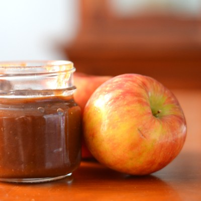 crockpot apple butter in a jar with apples