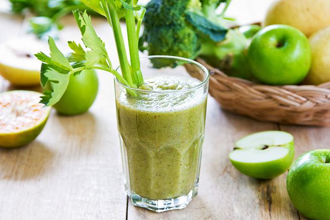 Vaso de bebida energética verde preparada con pera, apio y manzana