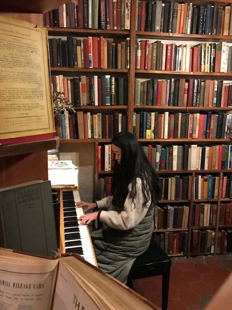 Ragazza che suona il pianoforte nella Shakespeare & Company di Parigi