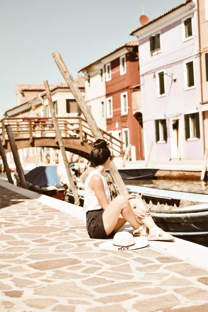 Lavinia Guglielman seduta tra i palazzi colorati di Burano