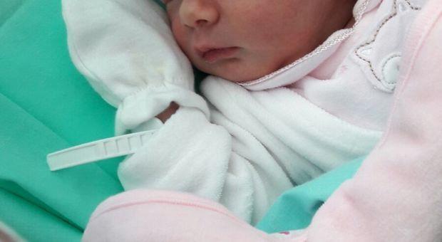 Le infermiere guardano affascinate la testa della neonata.