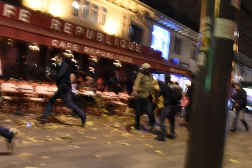 TOPSHOTS People run after hearing what is believed to be explosions or gun shots near Place de la Republique square in Paris on November 13, 2015. At least 18 people were killed in several shootings and explosions in Paris today, police said.  AFP PHOTO / DOMINIQUE FAGET