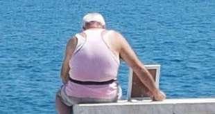 Porta la foto della moglie con se al mare. L'immagine virale che commuove il WEB