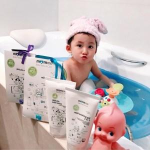 niño en la bañera con productos de baño