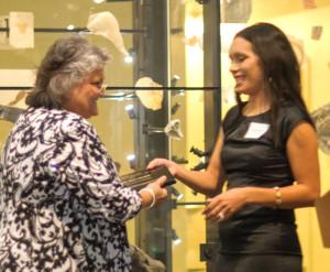 Narda Beas-Nordell, '92, receives the Pete Suazo Community Service Award from UMBA President Melinda Bowen (right). ©2014 All Smiles Photography