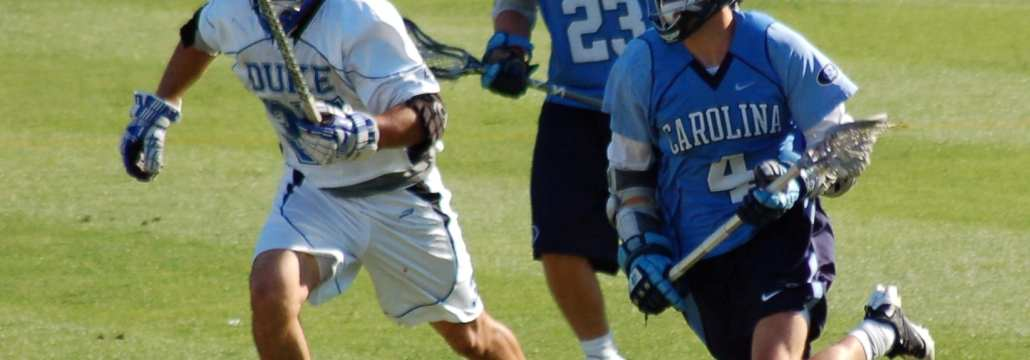 Duke Lacrosse long stick midfielder LSM pursues the NorthCarolina midfielder carrying the ball