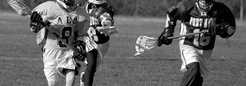 youth lacrosse defenders chasing the ball