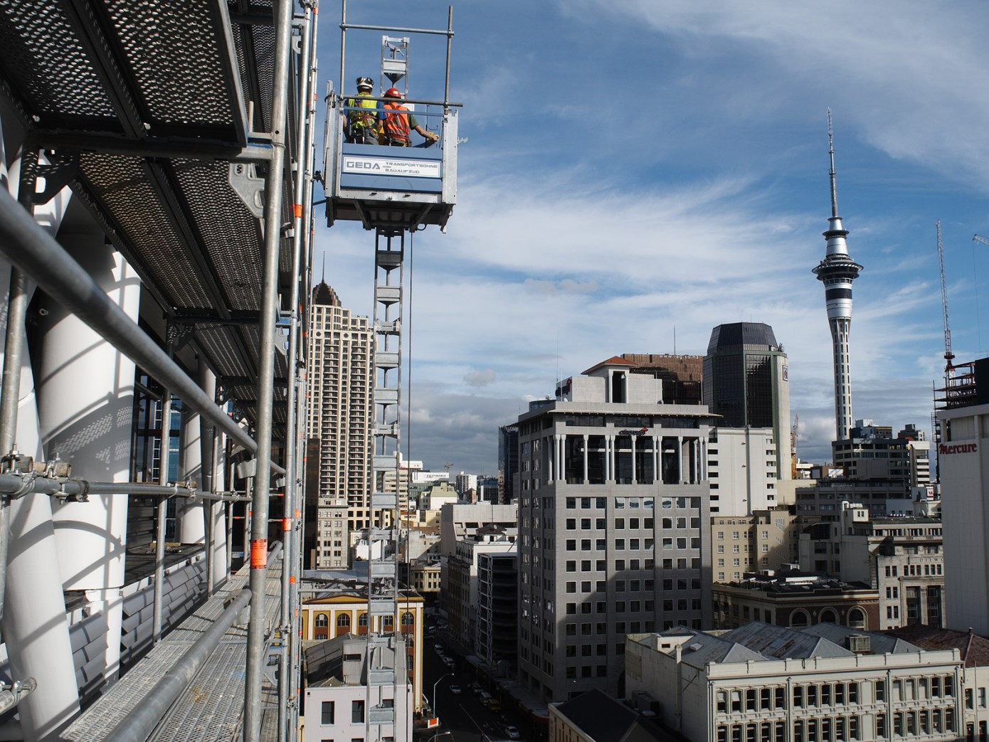 Scaffold hoist lifting people and materials overlooking Auckland's Sky Tower