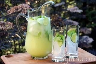 Servir la limonade à la Vodka avec des tranches de citron vert et des feuilles de menthe