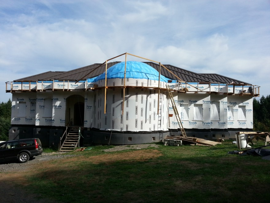 This is the most recent picture I took of the exterior of the house. You probably noticed the roof wasn't completely done at this point. You can see the scaffolding wrapping around the upper perimeter of the house and some bracing going above the dome we were using to keep rain off before the blue waterproofing membrane was applied to the dome.