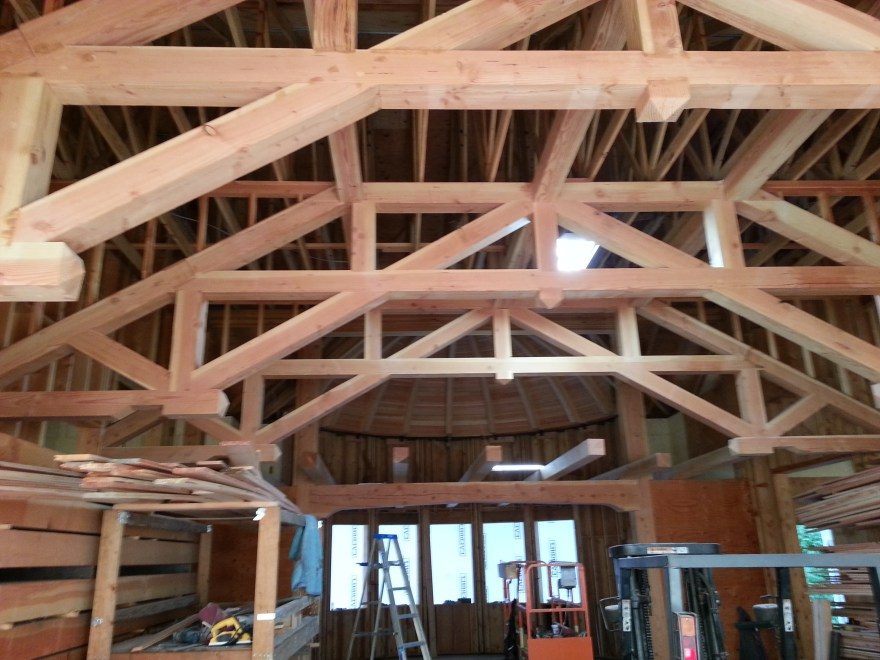 This is a picture from inside the great room looking towards the upstairs office. You can see the timber frame trusses that support the ceiling of the great room and some of the other really nice wood beams that support the west end of the engineered trusses that make up the actual roof.
