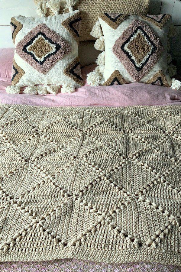 beige granny crochet blanket on bed