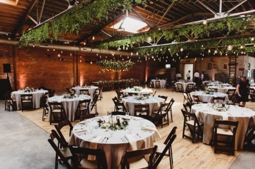 Greenery hung from ceiling of modern industrial wedding venue