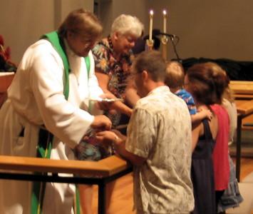 Pastor Jeff serves communion at the altar rail.