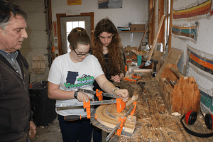 Two students at the workbench with a teacher