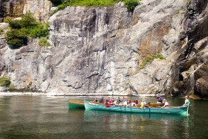 Image of kids and adults in two rowing boats with Lake Champlain cliffs behind them