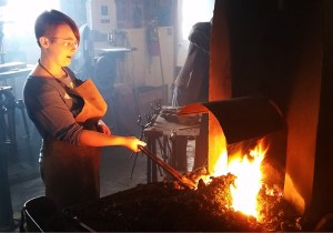A girl works a forge fire