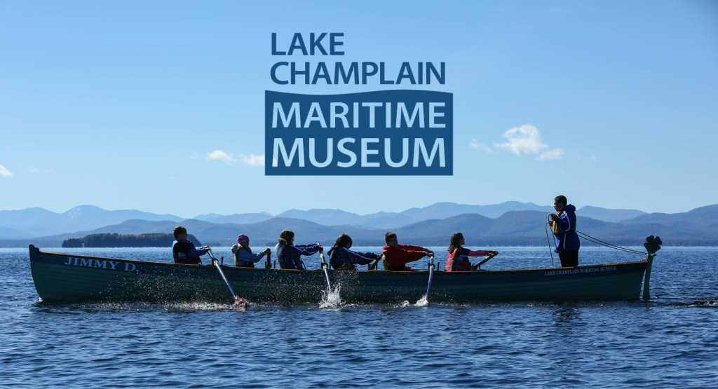 Students row in a longboat on Lake Champlain