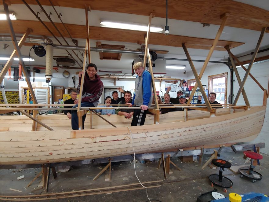 Students sit in and around a boat in the boat shop