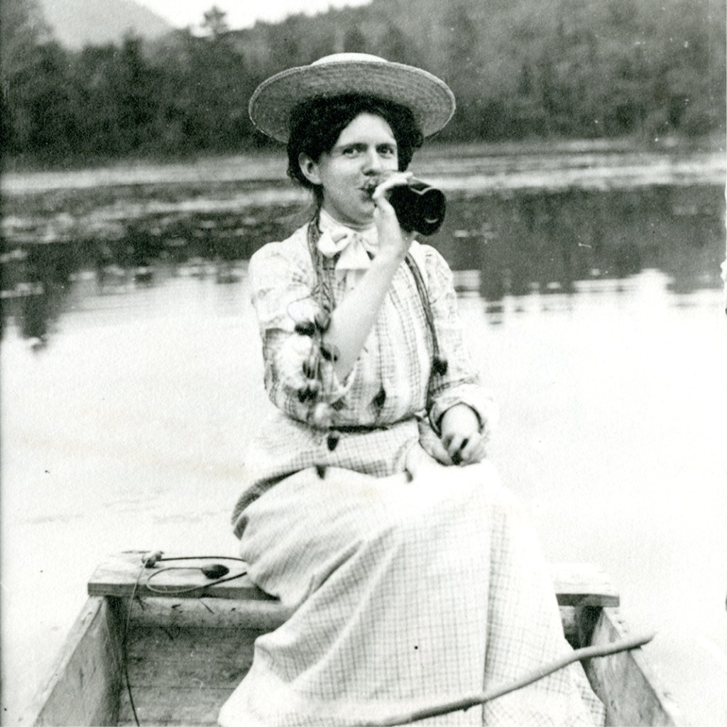 A black and white photograph of a woman wearing a wide-brimmed straw hat and long-sleeve full-length dress sitting on the back of a small row boat drinking from a dark colored glass bottle.