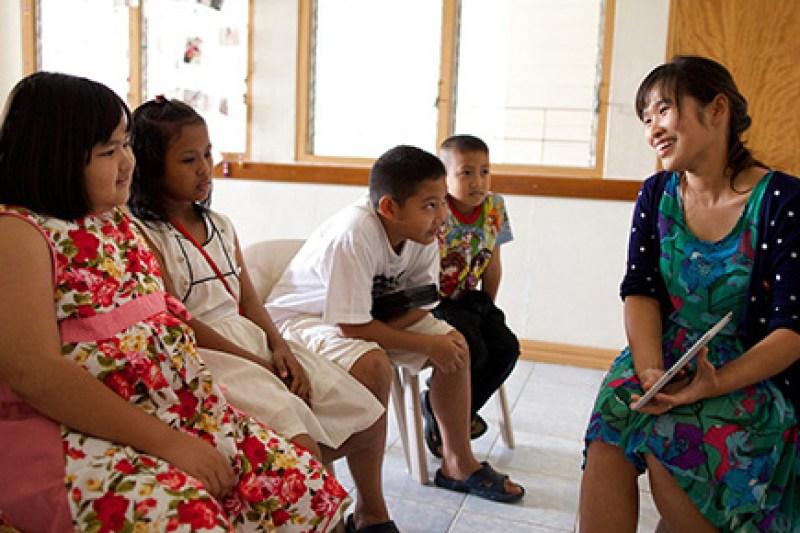Maestra muestra una tableta a alumnos de la Primaria