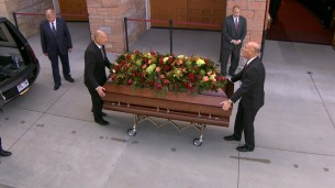 Beautiful flowers are placed careful on top of the casket.