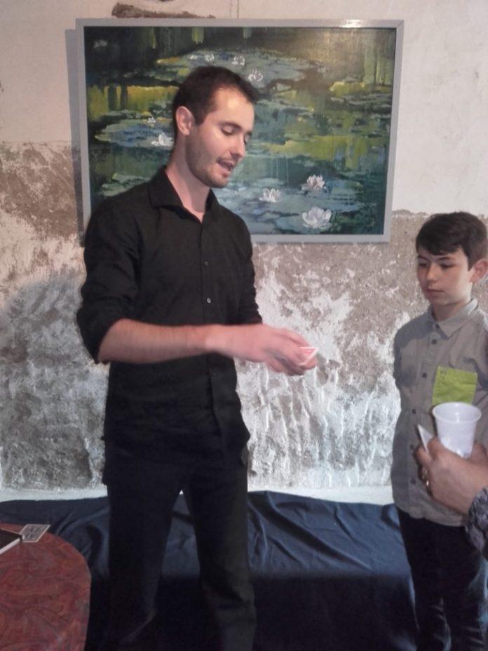 Arnault, le magicien, présentant un de ses tours à un jeune public enthousiaste