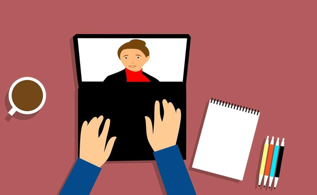 A graphic image of a laptop with a person on the screen. Two hands are typing on the keyboard. Next to the laptop is a coffee cup, a note pad and pens.