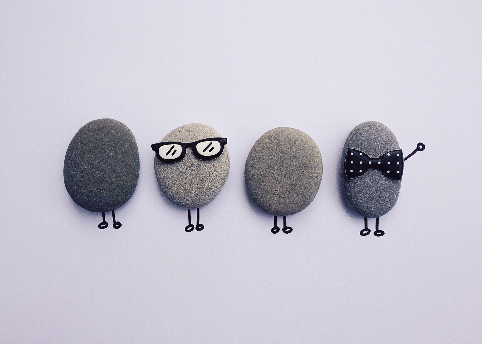 Four human like rocks with legs. One wearing shades and another wearing a bow tie