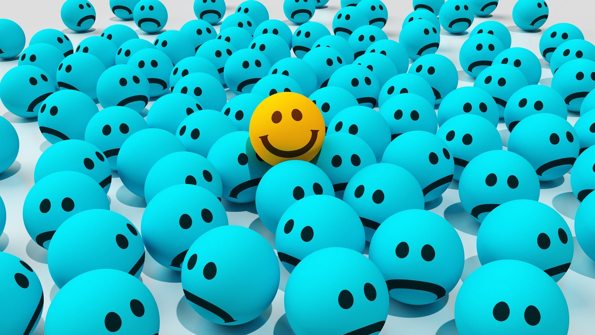 happy smiley face sticking out among other sad blue smiley faces