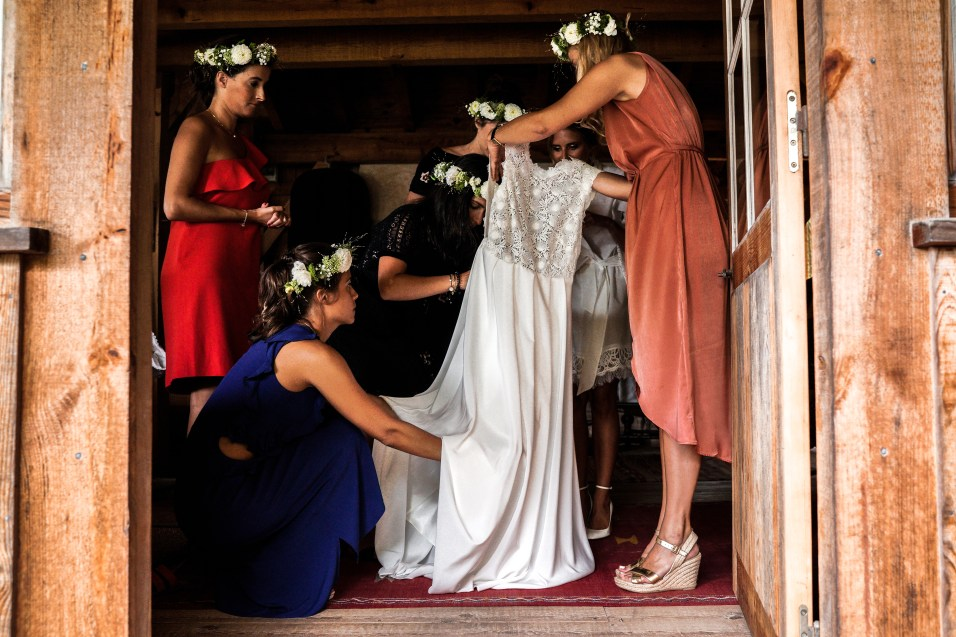 photo de la mariée qui enfilent sa robe avec ses témoins