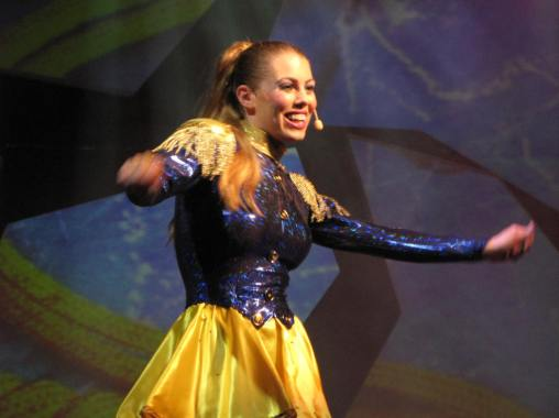 Leandra Ramm picture, singing and wearing sparkling dark blue and yellow dress