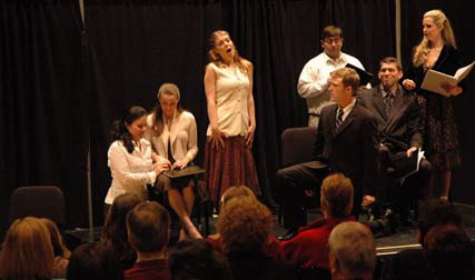 Leandra Ramm picture, wearing a white dress and brown blouse in a play