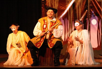 Leandra Ramm picture, wearing a crown, white mask and gown in a play