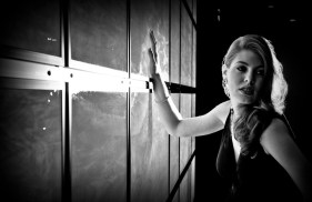 Leandra Ramm black & white picture, wearing black dress leaning on a window Take One