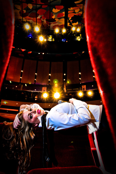 Leandra Ramm picture, wearing white dress laying on chairs and holding a mic