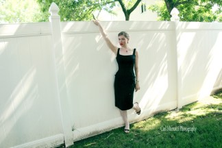 Leandra Ramm picture, wearing black dress leaning on a white fence Take Two