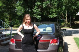Leandra Ramm picture, wearing black dress leaning on Honda Accord car Take One
