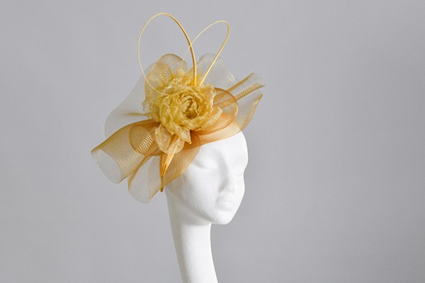 Golden Yellow tones Crinoline Fascinator perced on the front left on looking of the models head as she stares off to the right.