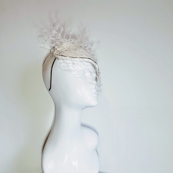 Ivory veiled bridal millinery on mannequin head.small2