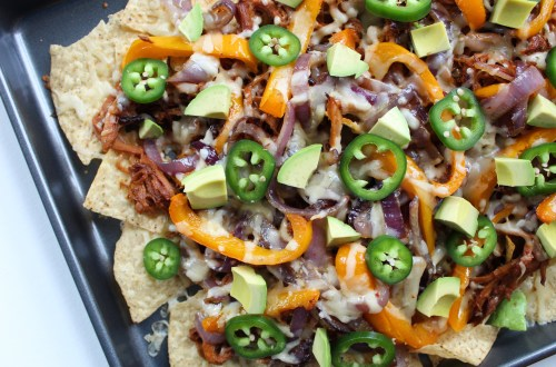 These nachos are topped with BBQ pork, fajita-style peppers and onions, and more fun toppings, and they'll make great party food!