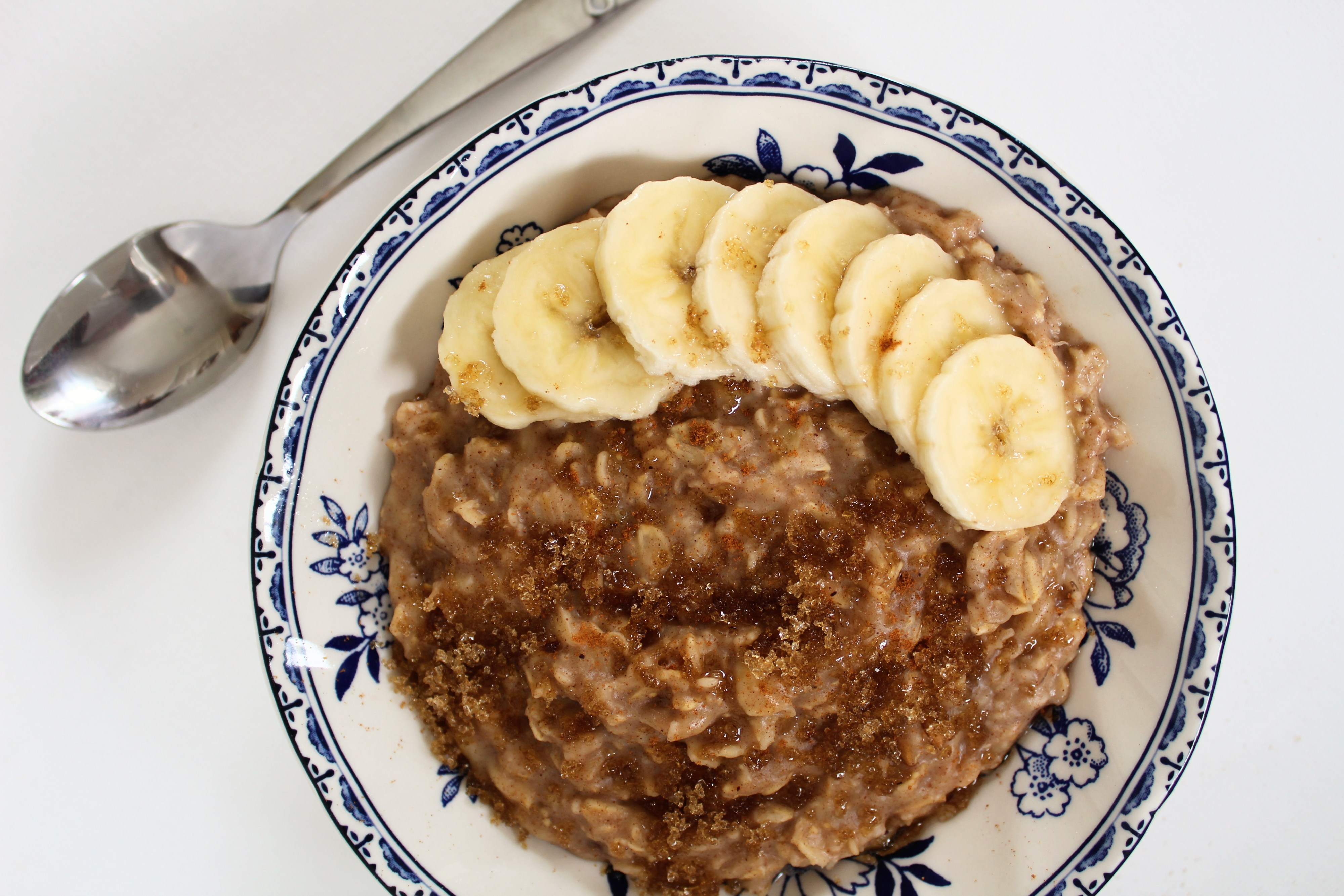 The warm & comforting flavors of banana bread make an easy breakfast in this creamy bowl of low-sugar banana bread oatmeal, topped with sliced bananas, cinnamon, and just a pinch of brown sugar.