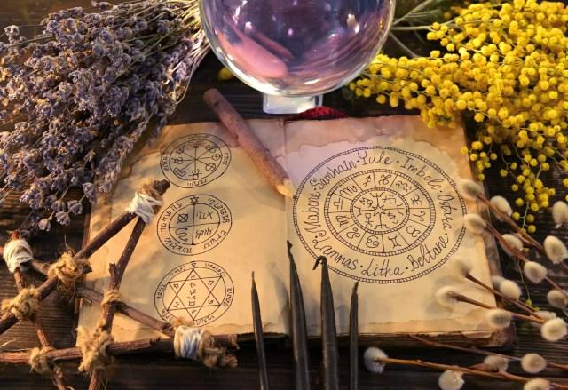 Carte veche cu grafic de sărbători wiccan, pentagram, bilă de cristal și ierburi.