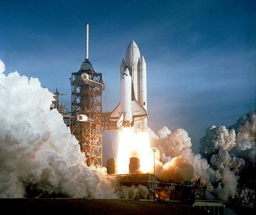 The space shuttle Columbia blasts off from the launch pad with lots of smoke and water vapour filling the sky.