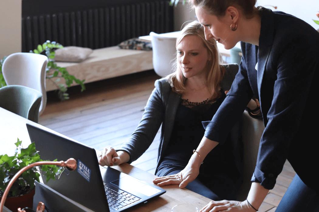 Τwo women looking at laptop screen.