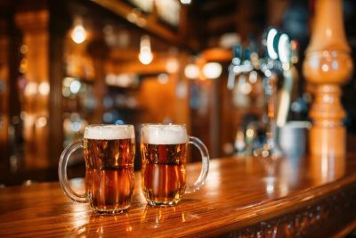 Two beer mugs on wooden bar counter, macro, nobody. Octoberfest symbol or concept. Glasses with golden beverage and foam on the table in pub, closeup view, blur background